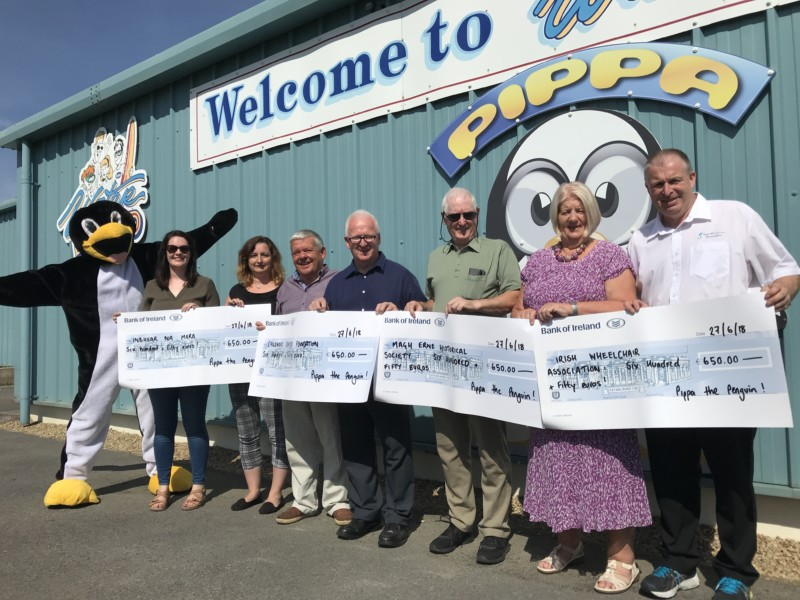 The beneficiary community and charity partners receiving their cheques from the proceeds of the annual charity day with Pippa The Penguin, Frankie O'Gorman and Anderson Keys of Waterworld